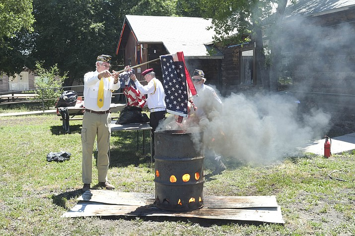 Charlie Bassett burns a retired American flag; a few of the hundred or so un-serviceable flags collected by the American Legion for retirement and members of the VFW and American Legion salute a retired flag.