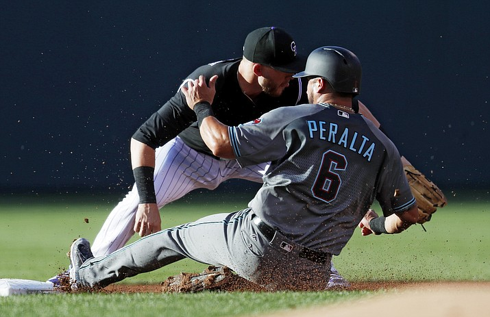 Arizona's David Peralta, front, slides safely into second base as he advances on a sacrifice fly hit by Paul Goldschmidt as Colorado Rockies shortstop Trevor Story fields the throw during Tuesday's game in Denver. (AP Photo/David Zalubowski)