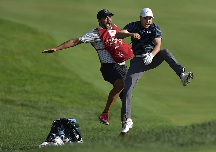 Jordan Spieth, right, celebrates with caddie Michael Greller after Spieth holed a bunker shot on a playoff hole on the 18th hole to win the Travelers Championship golf tournament Sunday, June 25, in Cromwell, Conn.  (Brad Horrigan/Hartford Courant via AP)