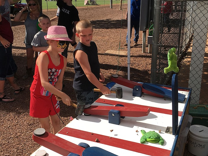 Ashley Lee of Chino Valley tries to hammer her toy frog toward the target during the 2016 Fourth of July celebration at Community Park on Monday.