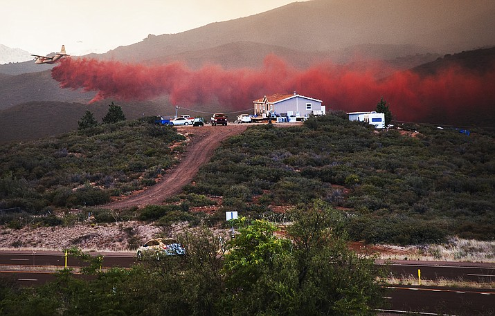 A plane drops retardant behind a home close to Highway 69 to protect it from the Goodwin Fire on Tuesday, June 27, near Mayer.