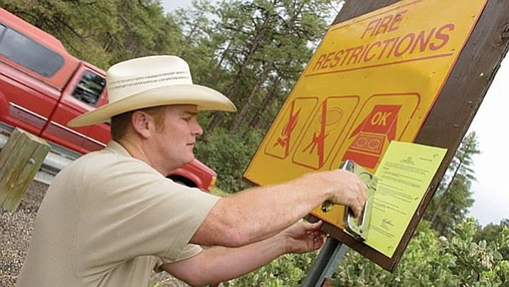Sean West, a Prescott National Forest prevention officer for the West Zone, in this 2009 file photo, posts fire restriction orders on a sign north of Goldwater Lake on Senator Highway in Prescott. On June 30, 2017, the forest and the greater Prescott area enters Stage II Fire Restrictions.