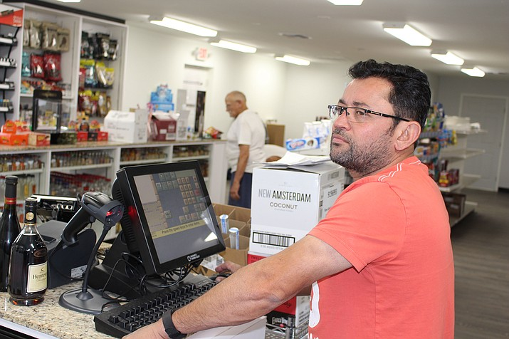 Hetal Dave, owner of Byers Liquor and Convenience store at 3019 Northern Ave., works on getting the store fully stocked Thursday after reopening nearly a year after the liquor store was destroyed by fire.