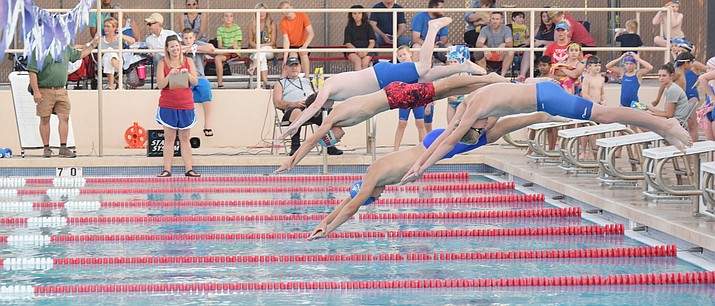 Cottonwood Clippers 15 and over boys swimmers dive into the pool at the Cottonwood Recreation Center Pool in the 50-yard butterfly on Friday night. The Clippers hosted the Red and White Meet, an intrasquad competition. (VVN/James Kelley)