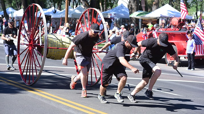 A Prescott Nantional Forest fire crew hauls their hosecart during the annual hose cart races on Cortez Street in downtown Prescott Sunday, July 2. The annual event dates back to possibly the late 1800's or early 1900's when Prescott had a volunteer fire department that consisted of the Toughs, Dudes and Mechanics.  (Les Stukenberg/Courier)