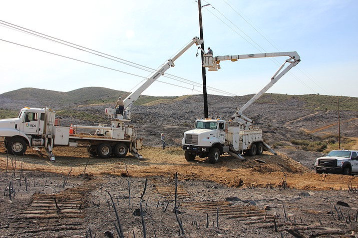 Arizona Public Service crews work to replace poles that were damaged after the Goodwin Fire jumped over Highway 69 on Tuesday, June 27.