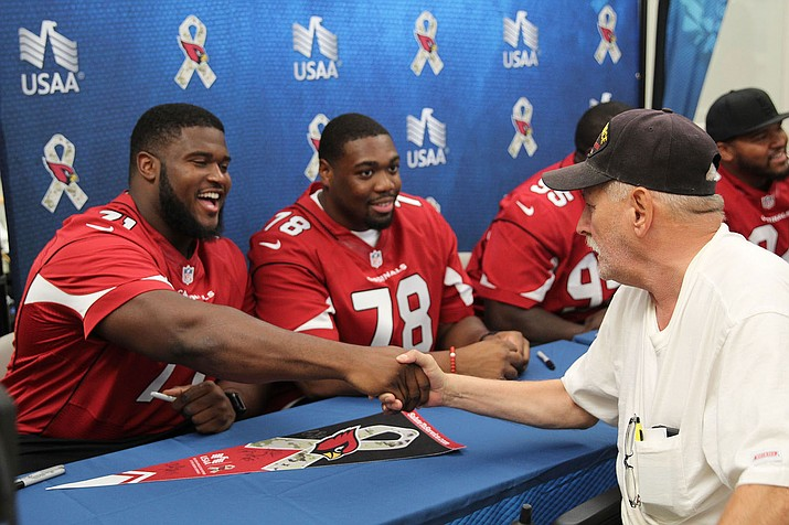 "Arizona's Kaleb Johnson shakes hands with a military veteran at the ""Salute to Service"" visit held at the VA Phoenix Hospital."