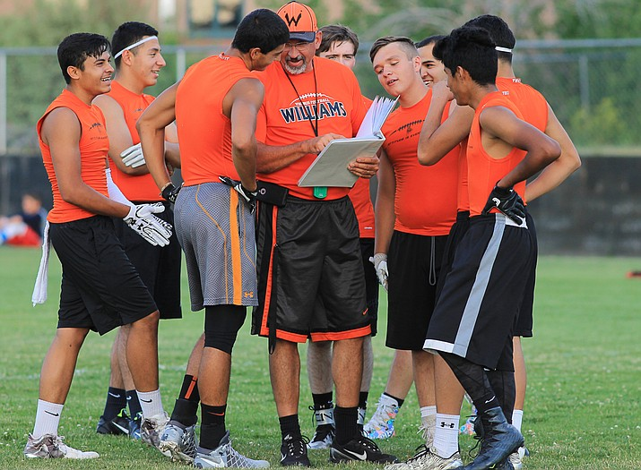 Coach Jeff Brownlee goes over passing plays with the Vikings during the summer ball 5-on-5 passing league.