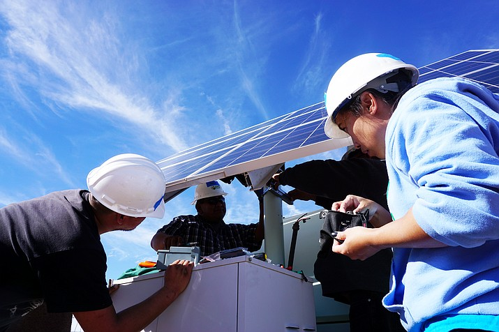 Grid Alternatives installs solar systems on approximately 40 reservations and trains Native American solar workers. Workers install solar panels on a house in Arizona.