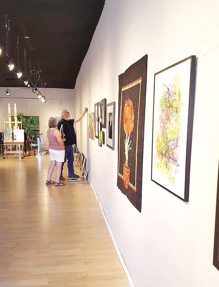 "Volunteers Paul VerBurg and Sally Bradley hang community pieces for the upcoming ""Kingman Flower Show"" at the Kingman Center for the Arts Gallery."