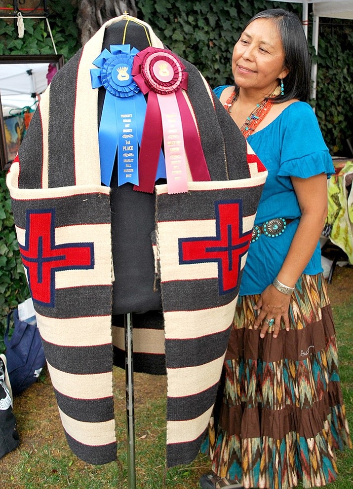 Tahnibaa Naataanii admires the Best of Show and first-place ribbons for her hand-made native cape at the 20th annual Prescott Indian Art Market. Her cape won top honors at the weekend Indian Art Market, which continues today at Sharlot Hall Museum in downtown Prescott. (Ken Leja, Sharlot Hall Museum/Courtesy)