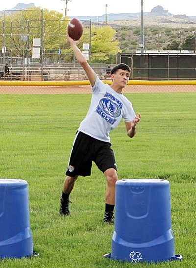 Kingman Academy senior-to-be quarterback Kekoa Makaiwi-Stroup fires a pass during the Tigers' spring football practice last year at Southside Park. The Arizona Interscholastic Association has approved year-round practice for sports.