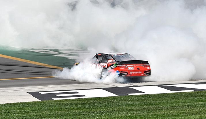 Xfinity Series driver Kyle Busch (18) blows his left rear tire as he does a burnout after his victory in the NASCAR Xfinity auto race at Kentucky Speedway, Saturday, July 8, 2017, in Sparta, Ky. (AP Photo/Timothy D. Easley)