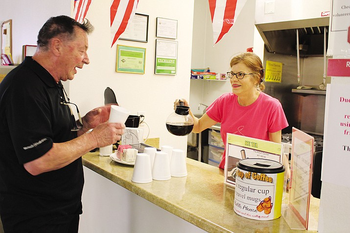 Pat Sajec, 78, gets a cup of coffee from his niece, Renee Zielke, a volunteer at Kathryn Heidenreich Adult Center. Sajec said his Social Security checks go a lot further in Kingman than they did in Seattle.