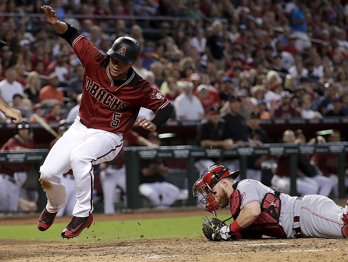 Arizona's Gregor Blanco (5) is tagged out by Cincinnati Reds catcher Tucker Barnhart after A.J. Pollock hit into a fielders choice during the fifth inning of a baseball game, Sunday, July 9, in Phoenix. (Matt York/AP)