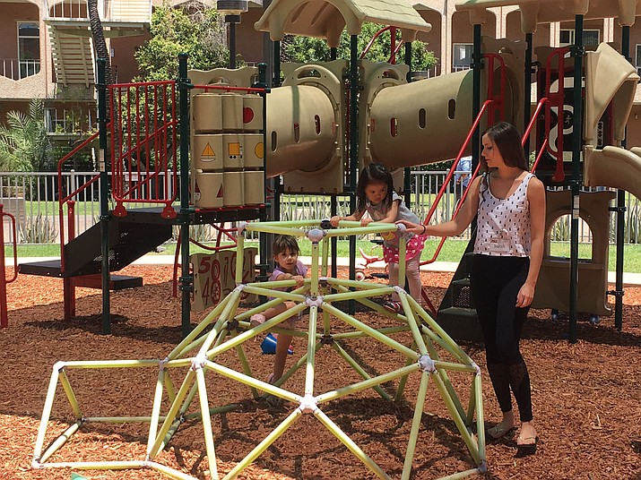 Children at the Child Study Lab Preschool play on the playground with undergraduate research student, Sarah Giedraitis, during break time.