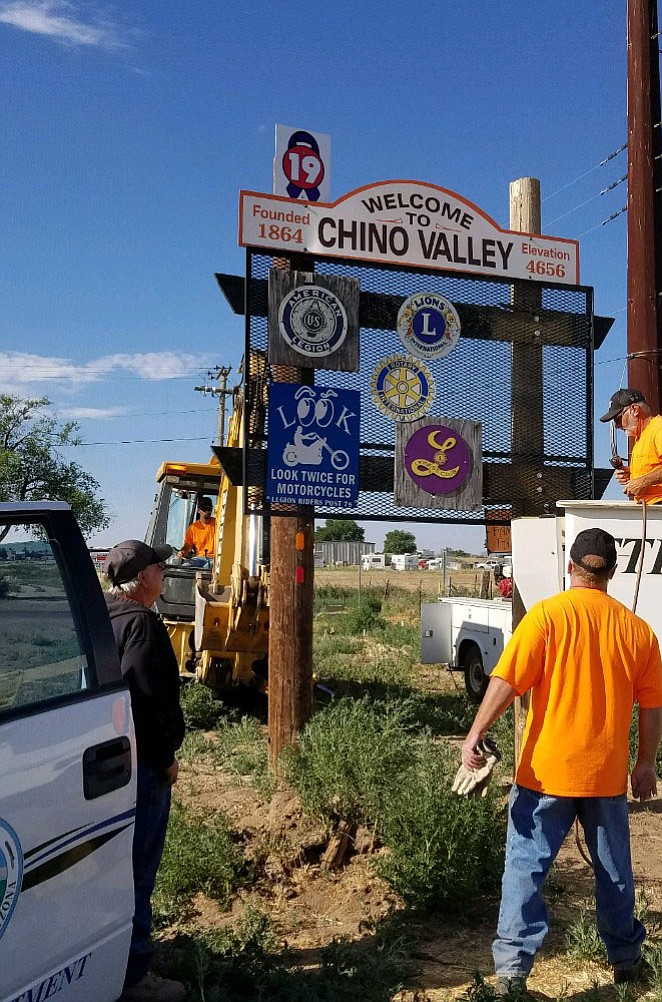 Chino Valley Public Works Department personnel fix the Welcome to Chino Valley sign at the north end of town on Thursday, July 6. It had been damaged about nine months ago.