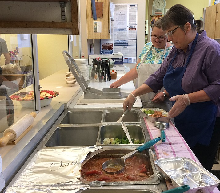 Volunteers dish out meals to be distributed to the many Chino Valley homebound residents.