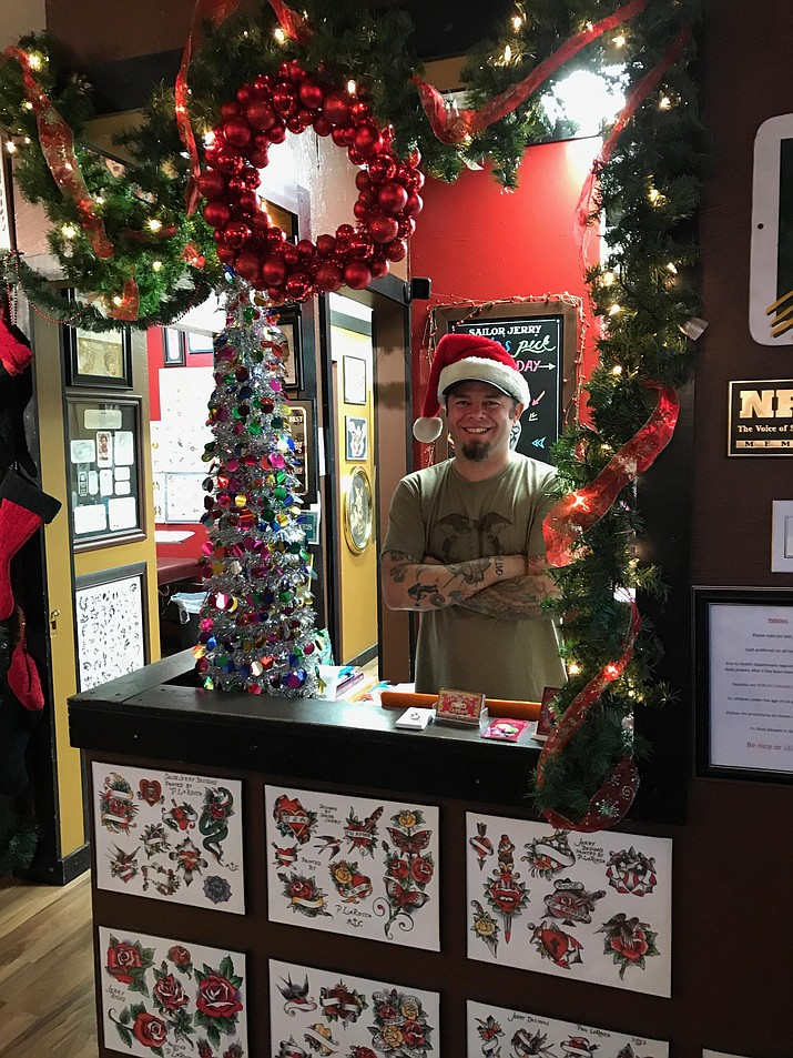 Leap of Faith Tattoo and Body Piercing owner Brian Randal stands in his shop, which is currently decked out in Christmas decorations for his Christmas in July event coming this Saturday, July 15.
