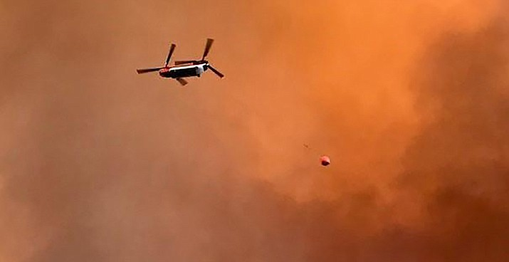 A Chinook helicopter flies over a wildfire. Officials say that when drones fly into restricted airspace over a wildfire they danger of collision forces firefighting aircraft like to be temporarily grounded. (Photo by Christina Montiel/via U.S. Forest Service)