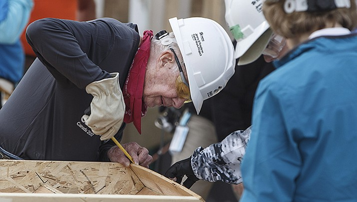 In this Tuesday, July 11, 2017 photo, former President Jimmy Carter helps build homes for Habitat for Humanity in Edmonton Alberta. Carter was back at a Habitat for Humanity worksite Friday, July 14, 2017, a day after he was hospitalized for dehydration while working with the organization to build homes for needy families in Canada.