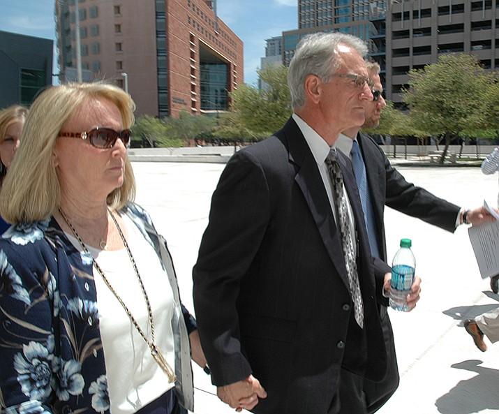 Sherry and Gary Pierce rush past reporters last month after they pleaded innocent in federal court to bribery and related charges in connection with votes he took while a member of the Arizona Corporation Commission. (Capitol Media Services photo, Howard Fischer)