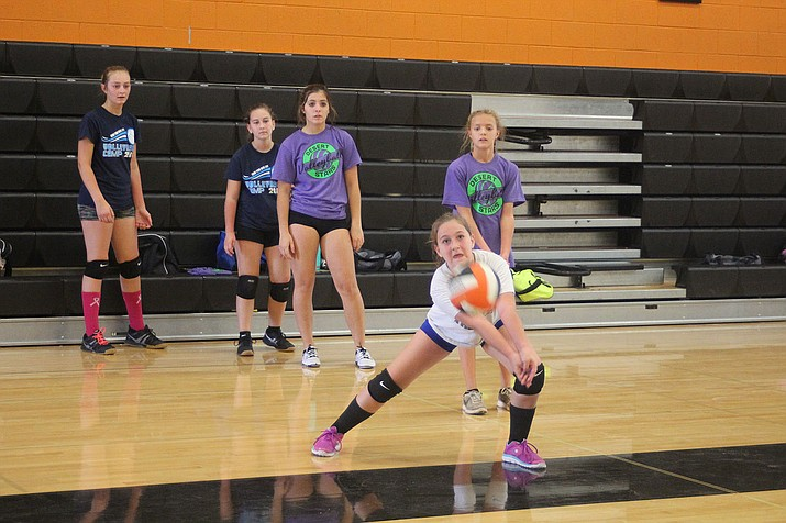 Kaydence Larsen, digs a volleyball Friday as other campers watch during the Desert Stars Volleyball camp at White Cliffs Middle School.