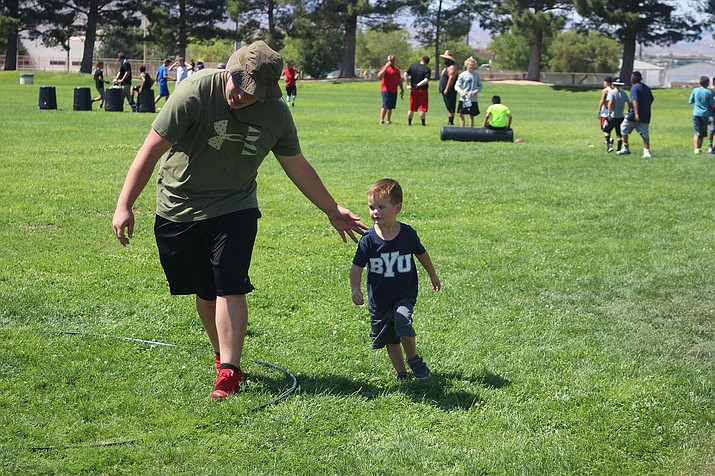 Maverick Jewett, 3, participates in a drill with the help of a coach.