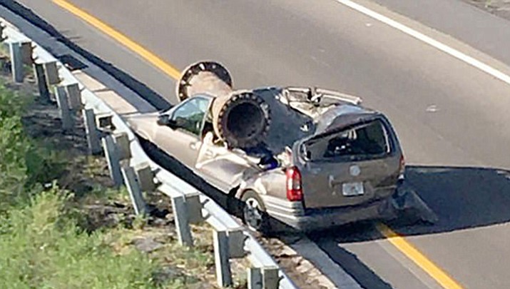 A truck loaded with scrap metal on an overpass above this van hit a guardrail and overturned, causing a huge industrial metal pipe to fall out and land directly on top of the driver's side of the vehicle. The driver escaped the freak accident with only minor injuries. (Florida Highway Patrol photo)
