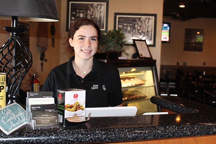 Taylor Henderson, 17, welcomes customers at Chophouse restaurant in Kingman, where she has worked since May. She's among the 43 percent of survey respondents who did not know about the new law that went into effect in July mandating paid sick leave for all employees.