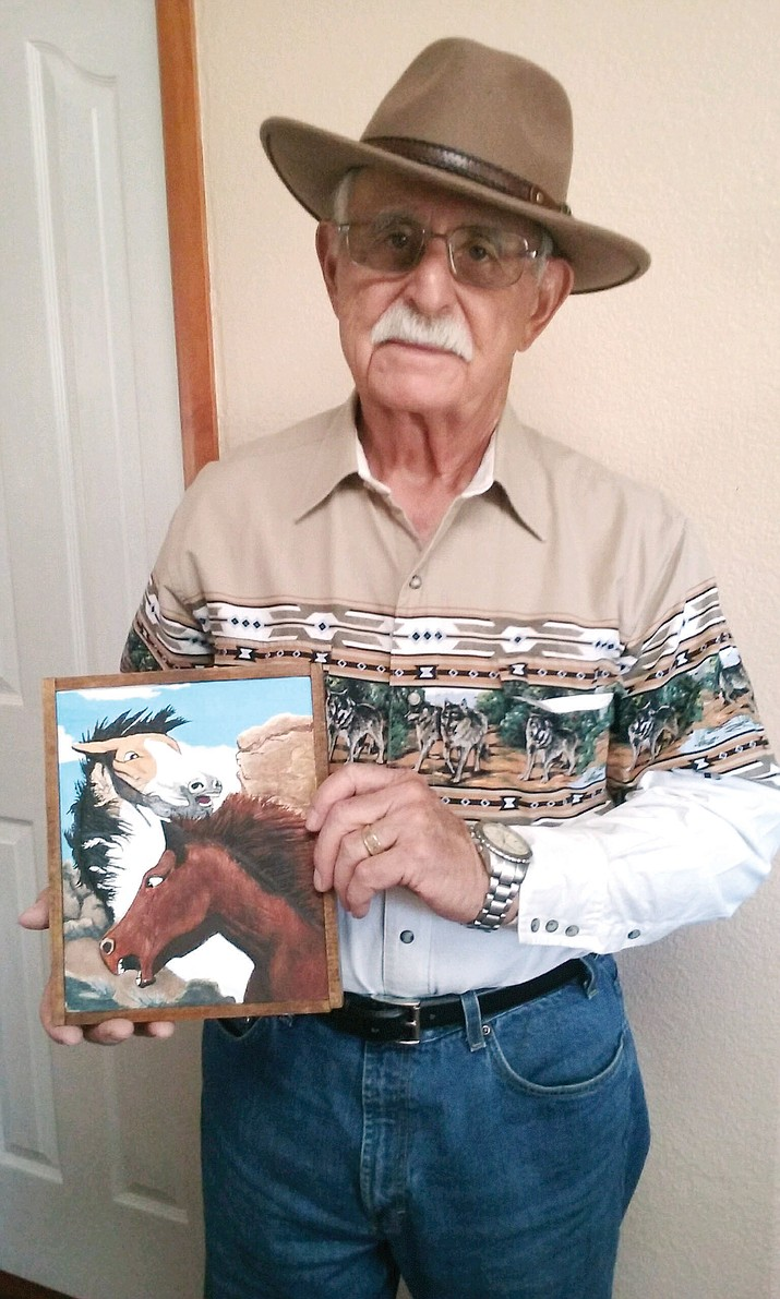 Robert Winsell shows off one of his relief wood carvings.