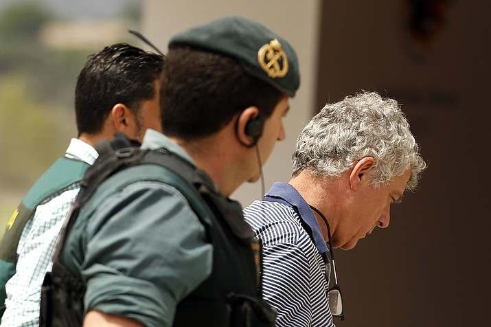 Former President of the Spanish Football Federation Angel Maria Villar, right, is lead by Spanish Civil Guard policeman to enter the Federation headquarters during an anti-corruption operation in Las Rozas, outside Madrid on Tuesday, July 18, 2017. (Francisco Seco/AP)