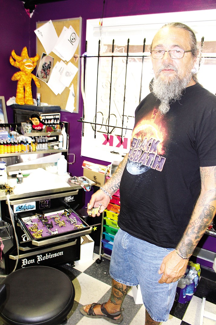 Don Robinson shows some of the expensive equipment used at Fine Tattoos. It costs about $15,000 to open a tattoo parlor.