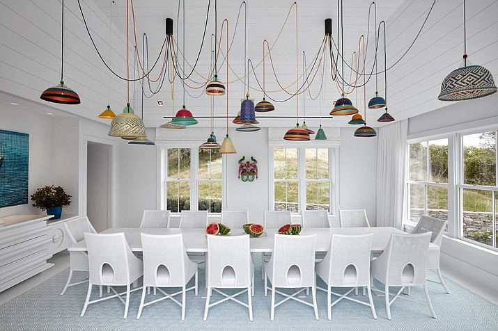 "This 2016 photo provided by Ghislaine Viñas Interior Design shows one of the rooms in a Montauk, N.Y. beach house with Ghislaine Viñas' design. The bold, colorful statement lighting becomes not only illumination but art in her design. Viñas used Alvaro Catalan de Ocon's PET Lamp chandelier, placing the colorful fixture in an all white dining space. ""It really pops and becomes a conversation piece,"" she says. (Garrett Rowland/Ghislaine Viñas Interior Design via AP)"