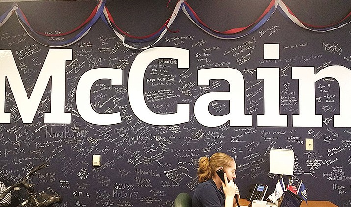 An intern answers phones at Sen. John McCain's Phoenix campaign headquarters in this 2016 file photo. The news this week that the Arizona Republican has an aggressive form of brain cancer brought messages of support from political heavyweights to pro athletes, from regular citizens to off-beat comedians.