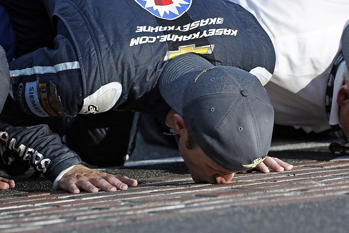 Kasey Kahne (5) kisses the yard of bricks on the start/finish line after winning the NASCAR Brickyard 400 auto race at Indianapolis Motor Speedway on Sunday, July 23. (AJ Mast/AP)
