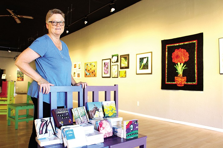 Pat Evans, secretary of Kingman Center for the Arts, shows some of the completed work on 6-inch-by-6-inch canvas pieces that will be part of the 6X6 on Route 66 Art Show that she hopes will raise $2,000 for the nonprofit organization.