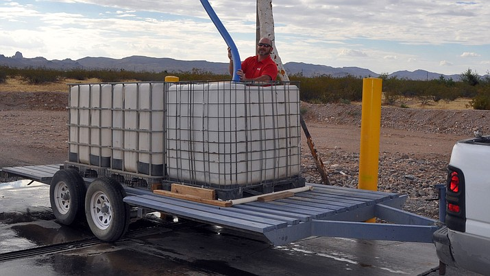 Golden Valley resident Michael Basile prepares to fill the three water cubes on his trailer at GVID standpipe located at Bolsa Drive and Estrella Road in Golden Valley.