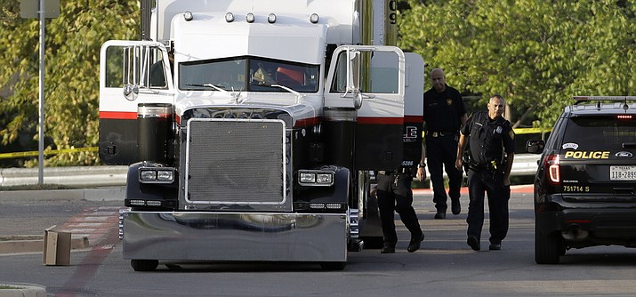 San Antonio police officers investigate the scene where nine people were found dead in a tractor-trailer loaded with at least 30 others outside a Walmart store in stifling summer heat in what police are calling a horrific human trafficking case. (Eric Gay/AP)