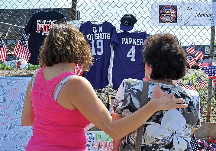 Debbie Hinds (left) comforts her mom, Madeline Ravelli, while looking at the memorial to the 19 Granite Mountain Hotshots outside of their base, Prescott Fire Station 7, on July 3, 2013. The station could be sold to a plumbing company this week. (Matt Hinshaw/Courier file)