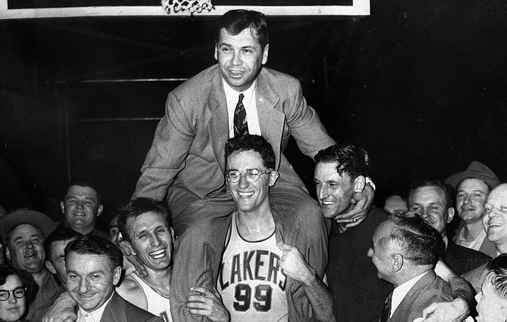 FILE - In this April 25, 1952, file photo, Minneapolis Lakers coach John Kundla, top, is carried by his players to their dressing room in Minneapolis after defeating the New York Knickerbockers to win their fourth NBA basketball championship in five years. Hall of Fame coach Kundla died Sunday, July 23, 2017. He was 101. (AP Photo/File)