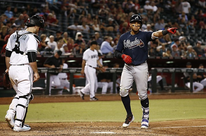 Atlanta Braves' Johan Camargo, right, points to his teammates as he arrives at home plate after hitting a home run as Arizona Diamondbacks' Chris Iannetta, left, looks down at home plate during the eighth inning Tuesday, July 25, 2017, in Phoenix. (Ross D. Franklin/AP)