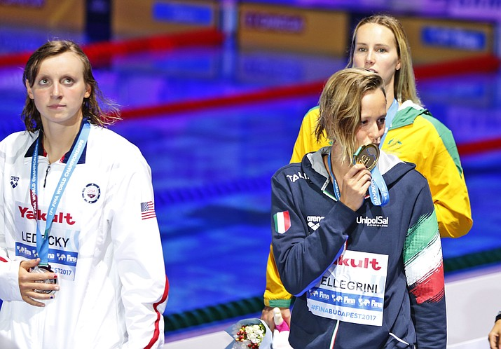 Italy's Federica Pellegrini, front right, kisses her medal as United States' silver medal winner Katie Ledecky, left, looks on after the women's 200-meter freestyle final at World Aquatics Championships in Budapest. Wednesday, July 26. (Darko Bandic/AP)