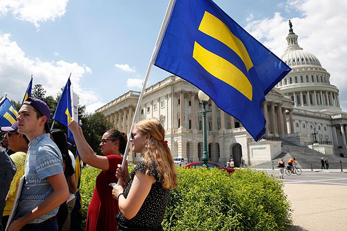 "People hold up ""equality flags"" on Capitol Hill in Washington, Wednesday, July 26, 2017, during an event held by Rep. Joe Kennedy, D-Mass., in support of transgender members of the military, in response to President Donald Trump's declaration that he wants transgender people barred from serving in the U.S. military ""in any capacity,"" citing ""tremendous medical costs and disruption."" (AP Photo/Jacquelyn Martin)"