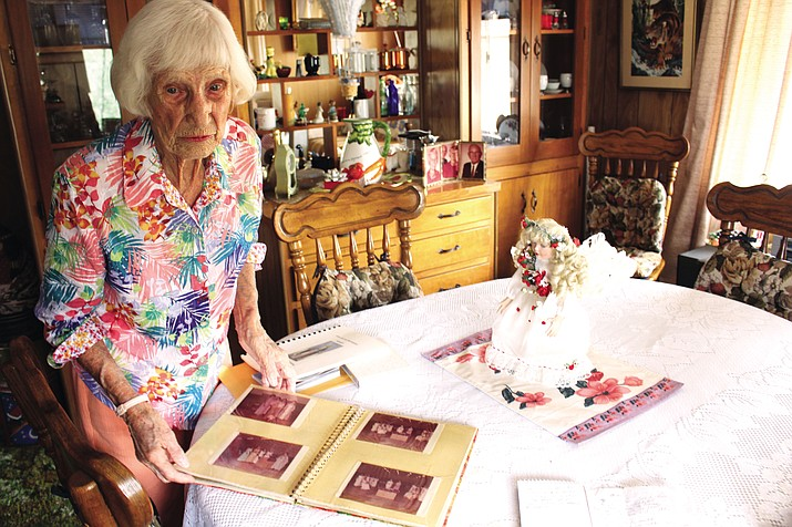 Addie Burdett, who turns 100 on Aug. 21, pages through photo albums at her home in Dolan Springs. She co-founded Our Lady of the Desert Roman Catholic church in Dolan Springs and attends mass every week.