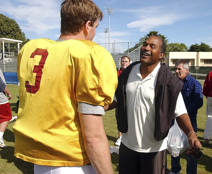 In this Dec. 28, 2002, file photo, University of Southern California quarterback Carson Palmer talks to O.J. Simpson after practice for the Orange Bowl in Davie, Fla. The two are winners of the Heisman trophy. USC head coach Todd Helton told reporters on July 27, 2017, that Simpson wouldn't be invited to watch practice or take part in any official functions at his alma mater this fall following his release from prison. (J. Pat Carter/AP, File)