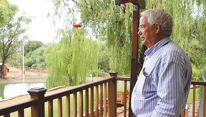 Mike Noble stands on his back porch, overlooking the designated area for RVs bordering his ranch.
