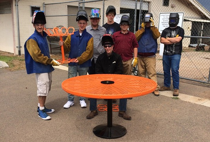 Student welders show completed projects from their welding class.