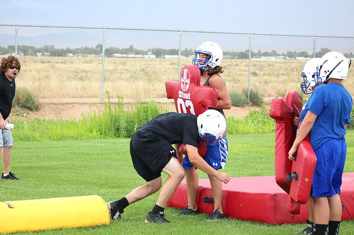 Two Kingman High School football players participate in a drill at practice Tuesday. The Bulldogs open the season Aug. 18 at home vs. Glendale's Joy Christian.