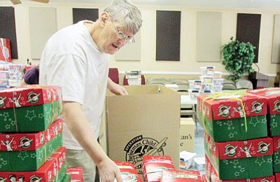 Mike Baldwin, Mohave County collection coordinator for Operation Christmas Child, packs shoeboxes filled with goodies that will be sent overseas to needy children.